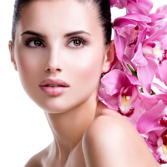 Close-upportret van mooie jonge mooie vrouw met gezonde huid en bloemen dicht bij gezicht - dat op wit wordt geïsoleerd.