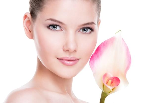 Close-upportret van mooie jonge mooie vrouw met gezonde huid en roze bloemen dichtbij gezicht - dat op wit wordt geïsoleerd.