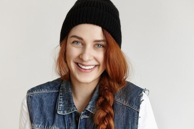 Close-upportret van mooie jonge roodharige europese vrouw die met vlecht gelukkig glimlacht