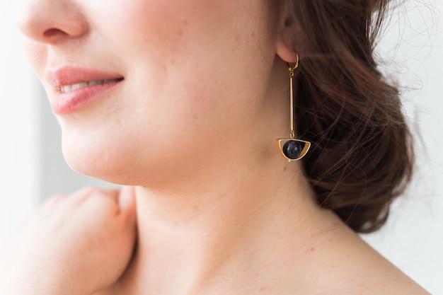 Close-upportret van mooie jonge vrouw met elegant kapsel en luxueuze juwelen en