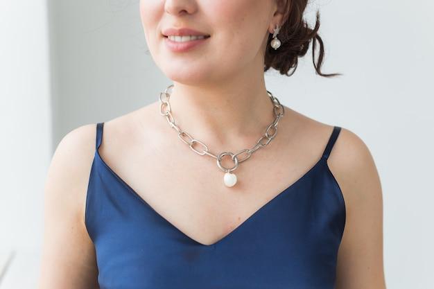 Close-upportret van mooie jonge vrouw met elegant kapsel en luxueuze juwelen