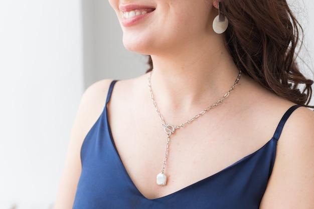 Close-upportret van mooie jonge vrouw met elegante luxueuze juwelen en bijouterie.