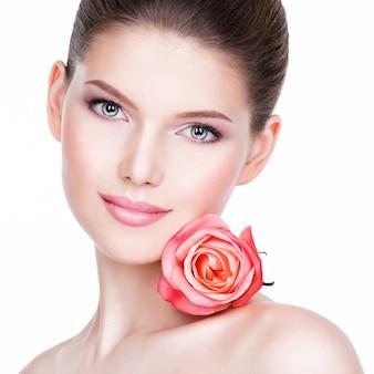 Close-upportret van mooie jonge vrouw met gezonde huid en bloem dichtbij gezicht - dat op wit wordt geïsoleerd.