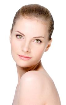 Close-upportret van mooie jonge vrouw met gezonde schone huid op een geïsoleerd gezicht -