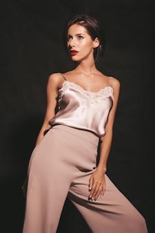 Close-upportret van mooie sensuele donkerbruine vrouw. meisje in elegante beige klassieke kleding. model met rode lippen geïsoleerd op zwart