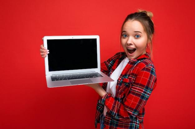 Close-upportret van mooie verbaasde jonge laptop van de vrouwenholding die rood overhemd draagt die camera bekijkt die op rode achtergrond wordt geïsoleerd. lege ruimte, uitsparing
