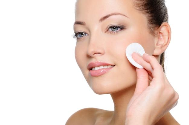 Close-upportret van mooie vrouw die haar mooi gezicht met wattenstaafje schoonmaken