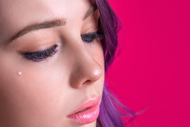 Close-upportret van mooie vrouw met roze haar en heldere lippen