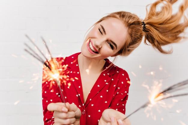 Close-upportret van onbezorgd meisje dat op witte muur met bengalen lichten wordt geïsoleerd. emotionele dame in rood nachtkostuum poseren met wonderkaarsen voor nieuwjaar.