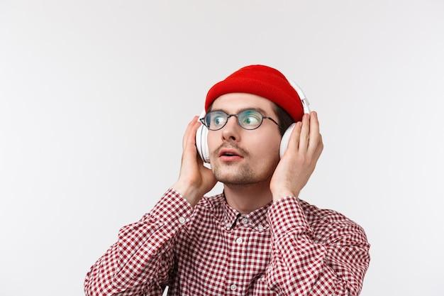 Close-upportret van opgewonden en overweldigde jonge hipstermens die nieuw album van zijn favoriete groep luisteren, hoofdtelefoons aanraken en verbaasd met verbaasde uitdrukking, witte muur kijken