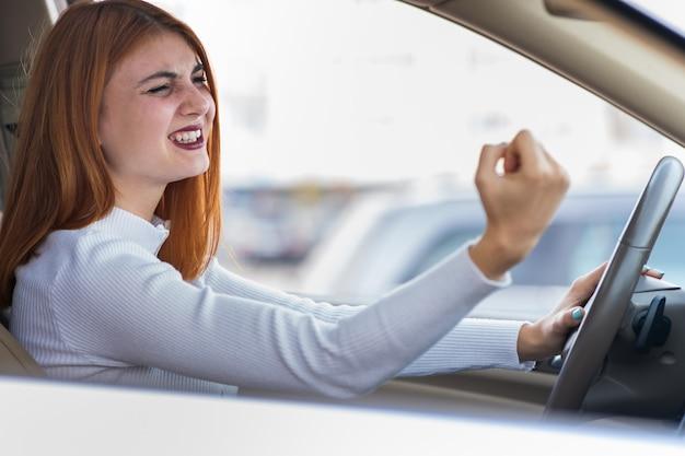 Close-upportret van pissig ontevreden boze agressieve vrouw die een auto drijft die bij iemand met omhoog handvuist schreeuwt.
