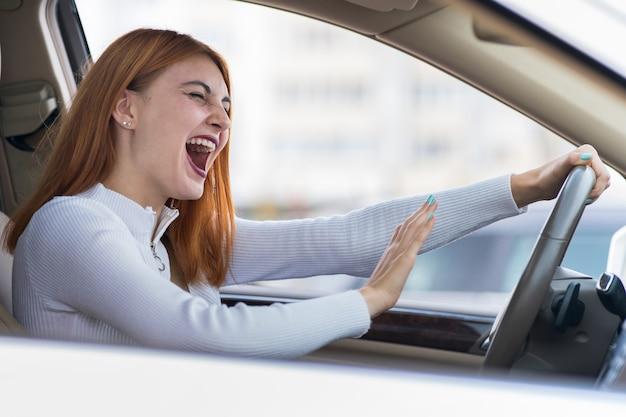 Close-upportret van pissig van ontstemde boze agressieve vrouw die een auto drijven die bij iemand schreeuwen