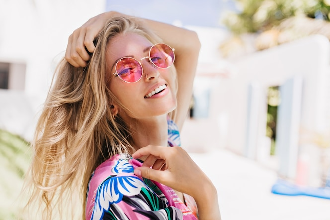Close-upportret van prachtig kaukasisch meisje in ronde roze zonnebril.