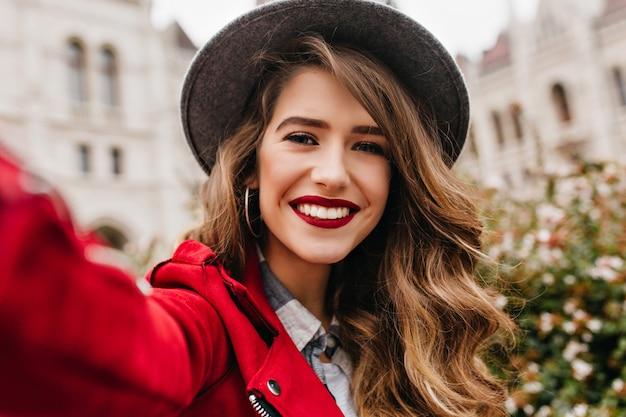 Close-upportret van prachtige vrouw met lichtbruin haar die selfie tijdens reis maken