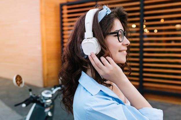 Close-upportret van romantisch krullend meisje in grote oortelefoons die gouden ring dragen