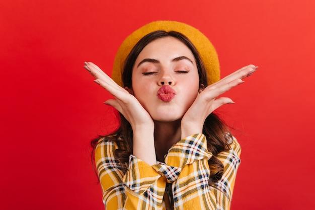 Close-upportret van roze-cheeked meisje dat luchtkus verzendt. vrouw in geruite blouse poseren met gesloten ogen in romantische sfeer.