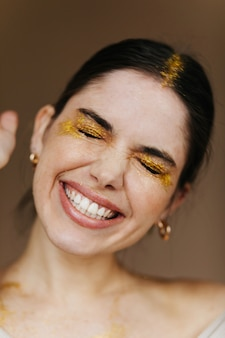 Close-upportret van schitterend vrouwelijk model in gouden toebehoren. aantrekkelijk donkerbruin meisje dat met gesloten ogen lacht.