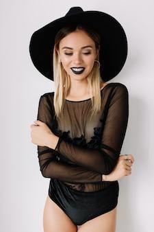 Close-upportret van schitterende blonde jonge vrouw die zwarte hoed en romper draagt