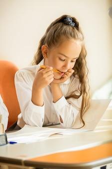 Close-upportret van schoolmeisje dat potlood kauwt terwijl ze huiswerk doet