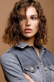 Close-upportret van schoonheidsmannequin met schone huid en krullend haar in het jasje van het jeansdenim, nat haar van model