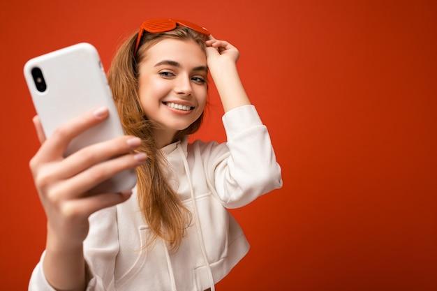 Close-upportret van sexy aantrekkelijke positieve glimlachende jonge blonde vrouw die modieuze witte hoodie draagt