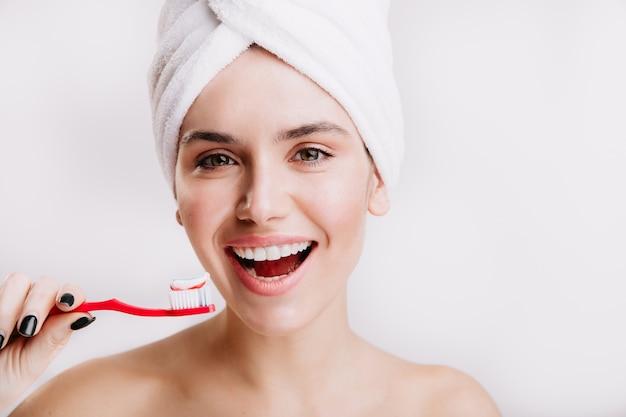 Close-upportret van tevreden meisje met handdoek op haar hoofd. brunette met sneeuwwitte glimlach houdt tandenborstel vast.
