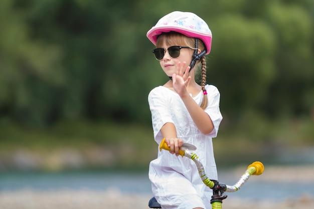 Close-upportret van trots vrij jong meisje in witte kleding, zonnebril met lange blonde vlechten die de roze fiets van het veiligheidshelm berijdende kindfiets dragen op vage groene het exemplaar ruimteachtergrond van de bomenzomer.