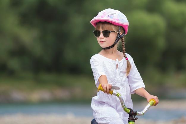 Close-upportret van trots vrij jong meisje in witte kleding, zonnebril met lange blonde vlechten die roze veiligheidshelm dragen die kindfiets berijden op vage groene bomen de zomer exemplaarruimte