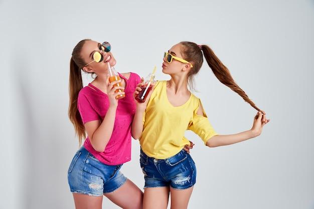 Close-upportret van twee persoons aardige leuke fascinerende mooie aantrekkelijke charmante vrolijke meisjes in vrijetijdskleding met drank die over witte achtergrond wordt geïsoleerd
