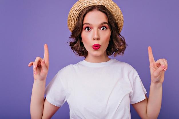 Close-upportret van verrast donkerogig meisje in de zomerhoed. binnen schot van grappig krullend vrouwelijk model in wit t-shirt poseren met vingers omhoog op paarse muur.
