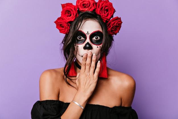 Close-upportret van verrast meisje met bruine ogen en make-up voor halloween. volwassen vrouw met kroon van rozen bedekt haar mond met haar hand tegen shock.