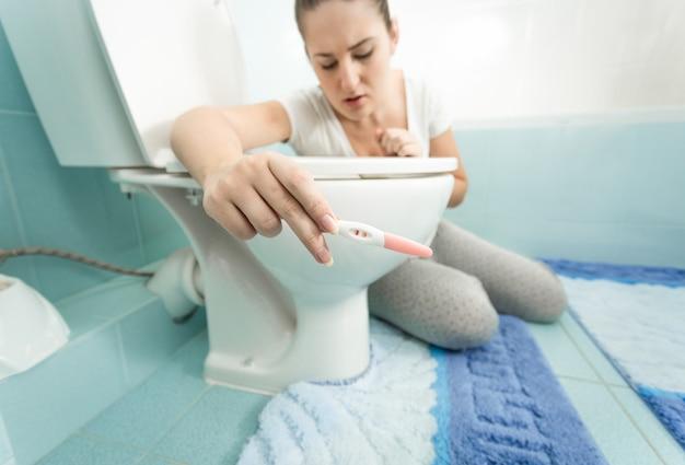 Close-upportret van verstoorde vrouw die positieve zwangerschapstest houdt bij badkamers