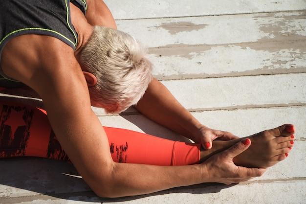 Close-upportret van volwassen blonde vrouw met de korte yoga van kapselpraktijken