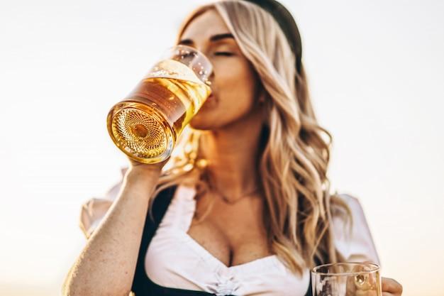 Close-upportret van vrij gelukkig blonde in dirndl, traditionele festivalkleding, die bier in openlucht drinken.