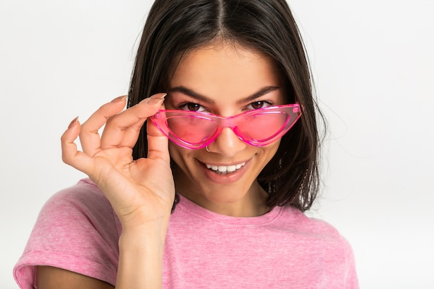 Close-upportret van vrij glimlachende emotionele vrouw in roze overhemd en modieuze zonnebril, witte tanden, positief geïsoleerd stellen