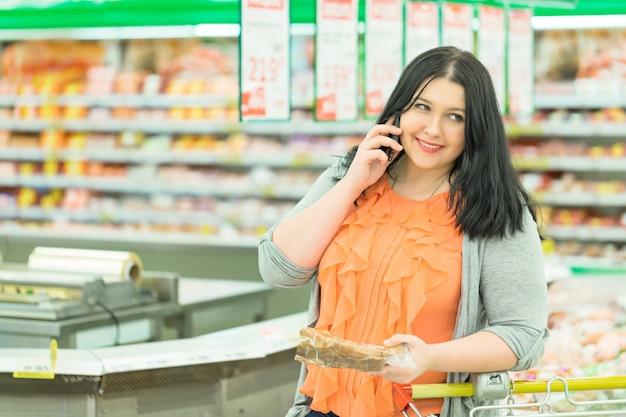 Close-upportret van vrij jong kaukasisch vrouwenbrunette die op de telefoon spreken en goederen in supermarktopslag kiezen