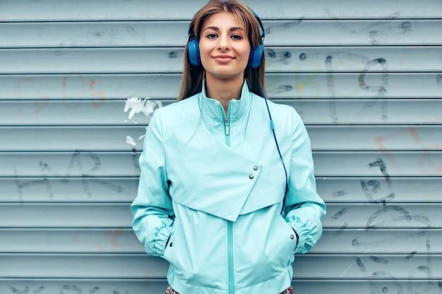 Close-upportret van vrij jonge vrouw die en het luisteren muziek glimlachen die zich op de straat met oortelefoons bevinden