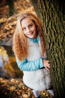 Close-upportret van vrij klein meisje dat en in herfstpark glimlacht rust