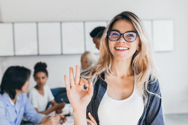 Close-upportret van vrij vrouwelijke manager van verkoopafdeling. indoor foto van lachende vrouw werkzaam in kantoor met mensen te bespreken.