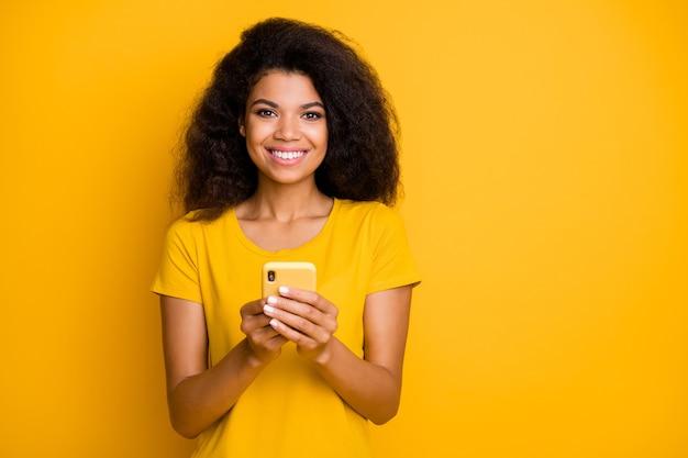 Close-upportret van vrolijk vrolijk zelfverzekerd meisje dat g gebruikt krijgt het verzenden van sms-bericht
