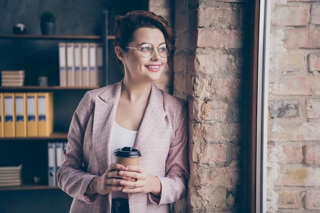 Close-upportret van vrolijke dromerige dame die venster bekijkt dat cacao drinkt