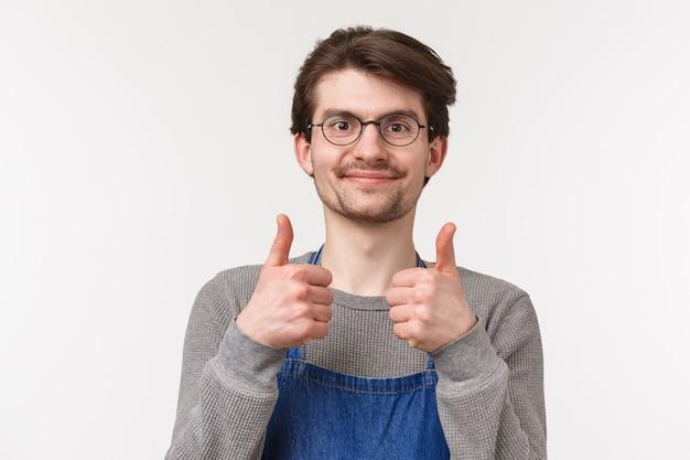 Close-upportret van vrolijke enthousiaste mannelijke werknemer gaat akkoord met collega, toont thumbs-up en glimlacht tevreden, geeft goedkeuring, garandeert beste kwaliteit koffie, staat