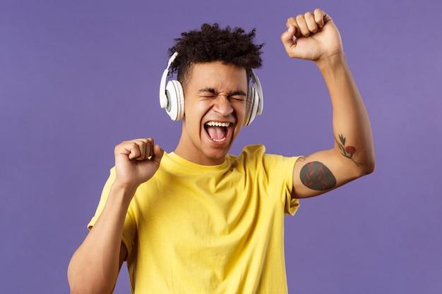 Close-upportret van vrolijke, gelukkige jonge dansende kerel heft hand op zingend, dichte ogen en vrolijk vrolijk glimlachend luisterend lied in hoofdtelefoons, genietend van muziek, purpere muur