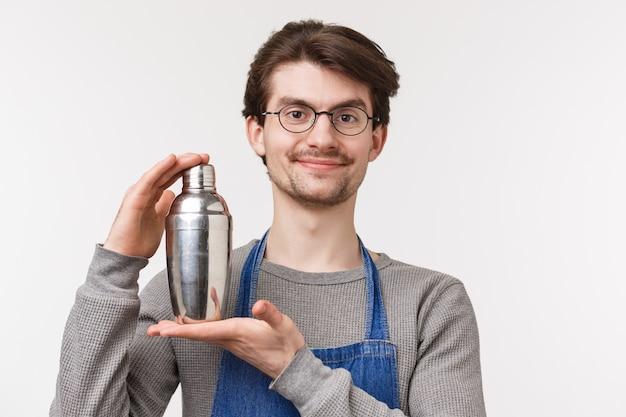 Close-upportret van vrolijke glimlachende jonge barman die bij het uitvinden van nieuwe cocktail werken, drank in schudbeker schudden en camera glimlachen, drank voor klant voorbereiden,