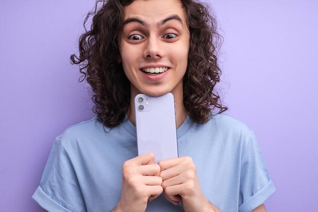 Close-upportret van vrolijke glimlachende kerel die foto op smartphone neemt die mobiele telefoon dicht bij ...