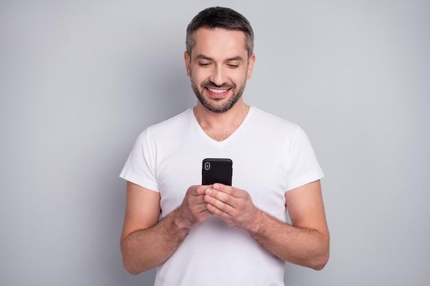 Close-upportret van vrolijke kerel die digitale telefoonglimlach gebruiken