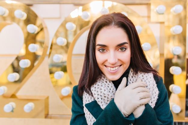 Close-upportret van vrolijke modieuze jonge vrouw met donkerbruin haar gesneden. stijlvolle stadsvooruitzichten, wintervakantiesfeer, glimlachen, echte emoties.