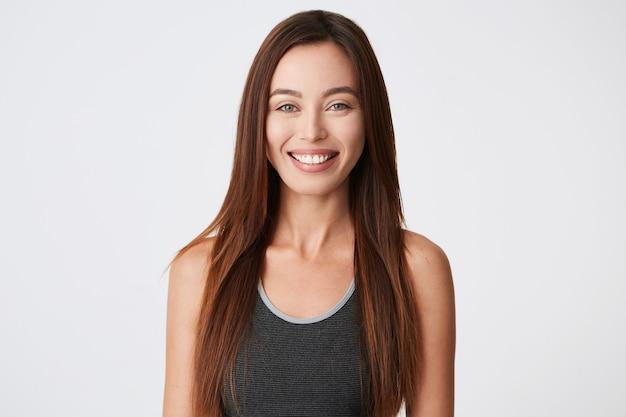 Close-upportret van vrolijke mooie jonge vrouw met donker lang haar en gezonde tanden die en zich zelfverzekerd glimlachen