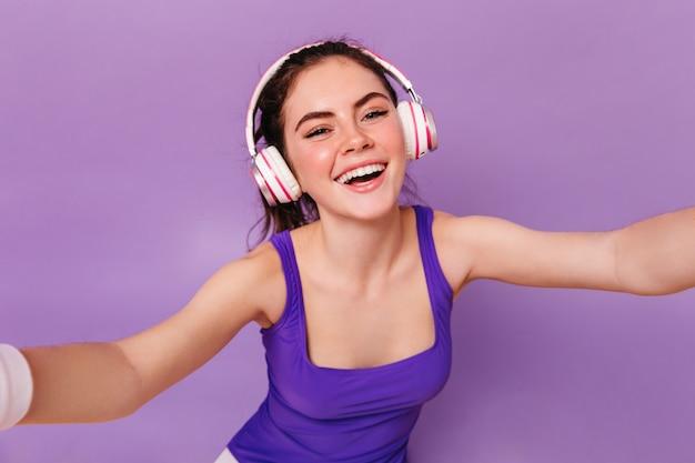 Close-upportret van vrolijke vrouw in geschiktheidsbovenkant en hoofdtelefoons die selfie op purpere muur nemen