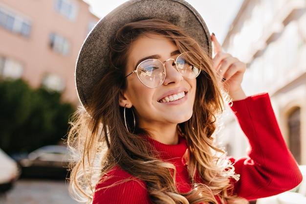 Close-upportret van vrolijke witte vrouw in glazen die haar hoed op onscherpte achtergrond raken